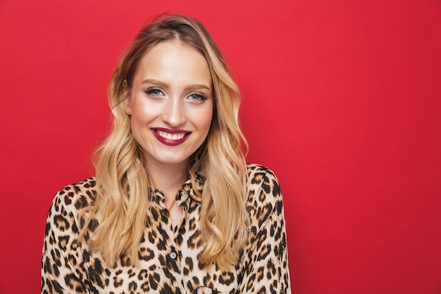 Close up of a beautiful young blonde woman standing isolated over red background