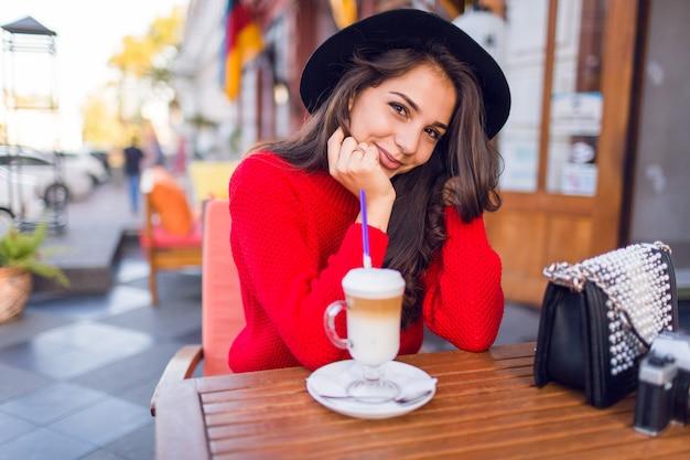 スタイリッシュな黒い帽子とオープンスペースのカフェに座っている明るい赤いセーターの美しい若いブルネットの女性を閉じて、晴れた朝に牛乳やカプチーノとコーヒーを飲みます。