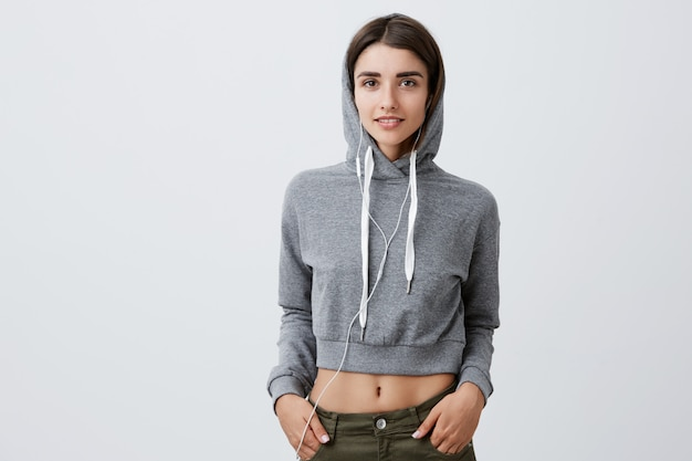 Close up of beautiful young caucasian girl with dark long hair wearing hoodie with cape on head holding hands in pockets, listening to music,