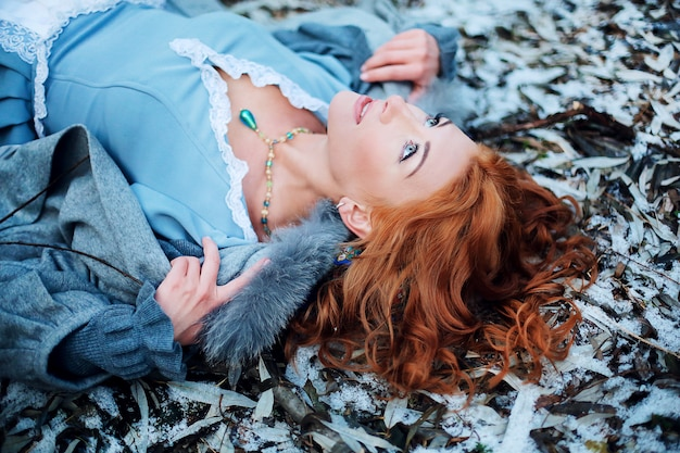 Close - up of a beautiful young girl with red hair and blue eyes lying on the snow looks at the sky in spring park.