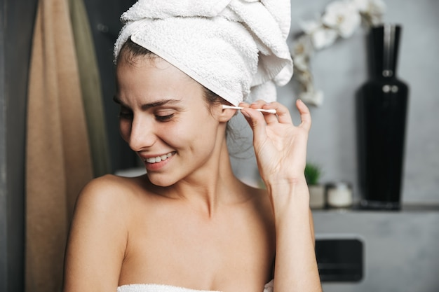 Close up of a beautiful young girl with towel wrapped around her head cleaning ears with cotton swab at the bathroom