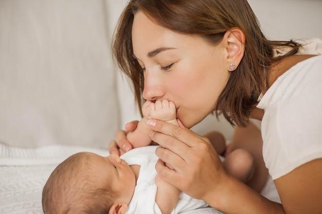 확대. 아름 다운 젊은 어머니는 아기를 키스. 아름 다운 젊은 어머니는 침대에서 아기와 함께 재생됩니다. 어머니.