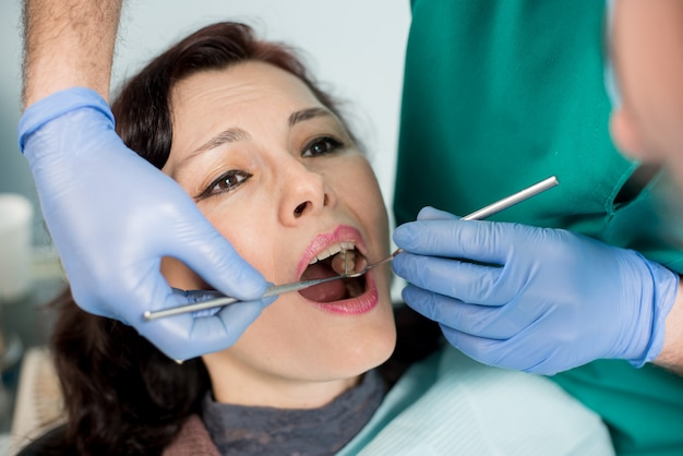 Close up of beautiful young woman having dental check up. dentist examining a patient's teeth, holding dental tools - mirror and probe. dentistry.