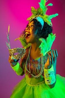 閉じる。カーニバルの美しい若い女性、ネオンの光のグラデーションの壁に羽を持つスタイリッシュな仮面舞踏会の衣装。休日のお祝い、お祭りの時間、ダンス、パーティー、楽しんでの概念。