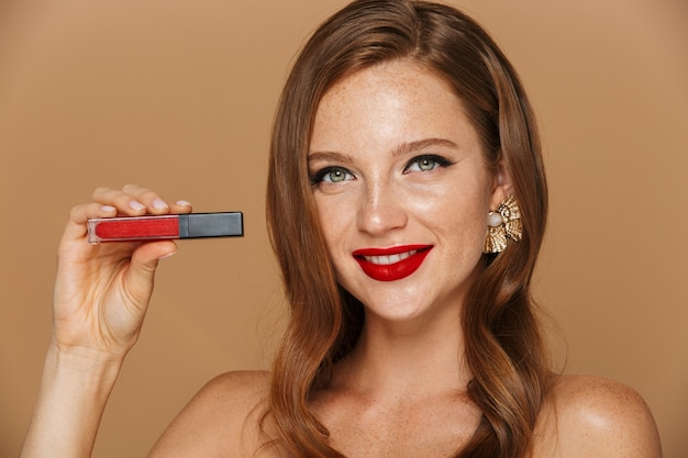 Close up of a beautiful young  woman wearing makeup and jewelry accessories posing isolated over beige wall, showing red lip gloss
