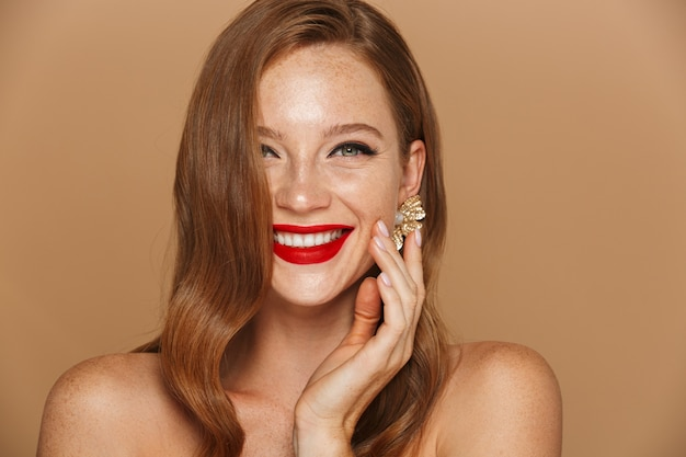 Close up of a beautiful young woman wearing makeup and jewelry accessories posing isolated over beige wall