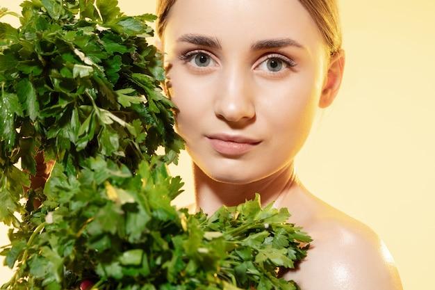 Primo piano di bella giovane donna con foglie verdi su bianco