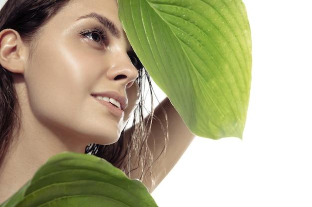 白い壁の顔の近くに緑の植物の葉を持つ美しい若い女性を閉じます。化粧品、メイクアップ、ナチュラル&エコトリートメント、スキンケアのコンセプト。光沢のある健康な肌、ファッション、ヘルスケア。