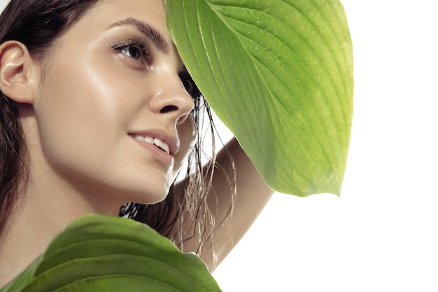 Close up beautiful young woman with green plant leaves near face on white wall. concept of cosmetics, makeup, natural and eco treatment, skin care. shiny and healthy skin, fashion, healthcare.