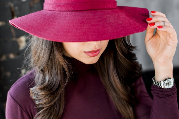 Close-up of a beautiful young woman with pink hat