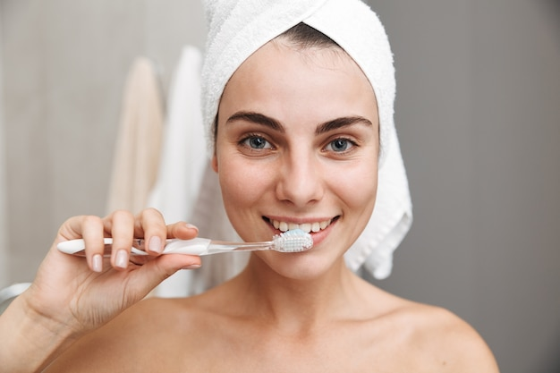 Close up of a beautiful young woman with towel on her head standing at the bathroom, brushing teeth