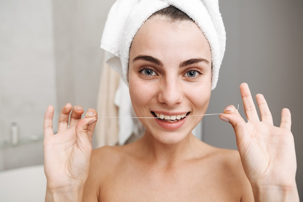 Close up of a beautiful young woman with towel on her head standing at the bathroom, using teeth floss