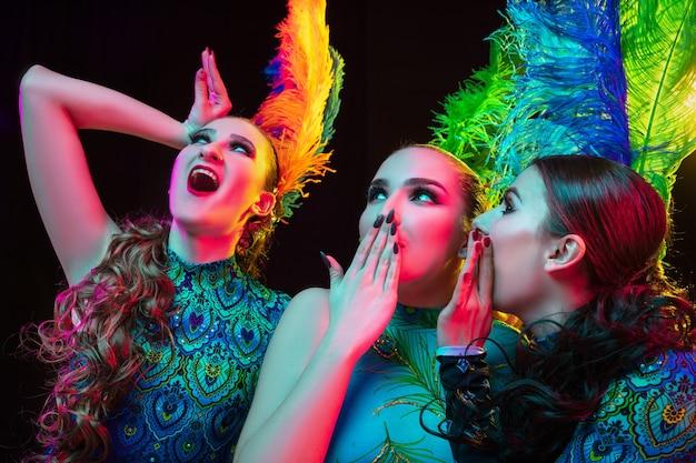 閉じる。カーニバルの美しい若い女性、ネオンの光の中で黒い背景に羽を持つスタイリッシュな仮面舞踏会の衣装。