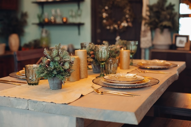 Close-up of beautifully decorated dining table with fir trees in vases and gold candles. sets of plates for four people.