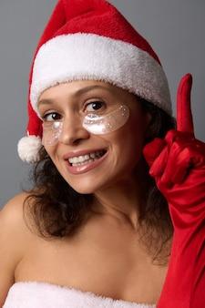 美しい笑顔、サンタの帽子をかぶって、目の下のパッチを滑らかにする魅力的な若いブルネットのクローズアップの美しさの顔の肖像画は、カメラを見て、灰色の背景のコピースペースに指を指します