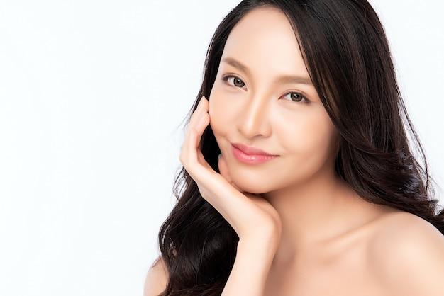Крупным планом красоты лица. усмехаясь портрет азиатской женщины касающий здоровый кожи. красивая счастливая девушка с свежей светящейся увлажненной кожей лица и естественным макияжем