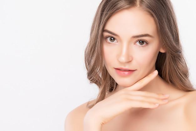 Закройте лицо красоты. улыбаясь азиатской женщины касаясь здоровой кожи портрета. красивая счастливая девушка-модель со свежей сияющей увлажненной кожей лица и естественным макияжем