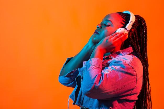 立っているドレッドヘアを身に着けている魅力的な若いアフリカの女性の美容ファッションの肖像画をクローズアップ