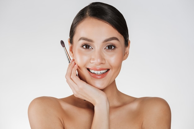 Chiuda sul ritratto di bellezza della donna adorabile del brunette con la spazzola molle di trucco della holding della pelle per le sopracciglia e la ricerca sulla macchina fotografica, isolata sopra la parete bianca
