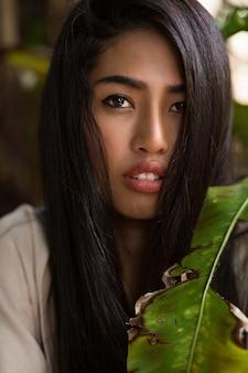 Chiuda sul ritratto di bellezza della donna asiatica con la pelle perfetta che posa nel giardino tropicale. capelli sani, labbra carnose.