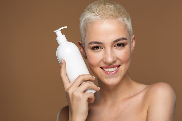 Close up beauty portrait of an attractive smiling young blonde woman with short hair posing isolated on brown, showing empty plastic container