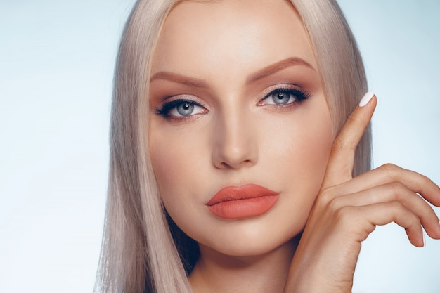 Close up beauty portrait of a blonde woman with perfect skin and plump lips