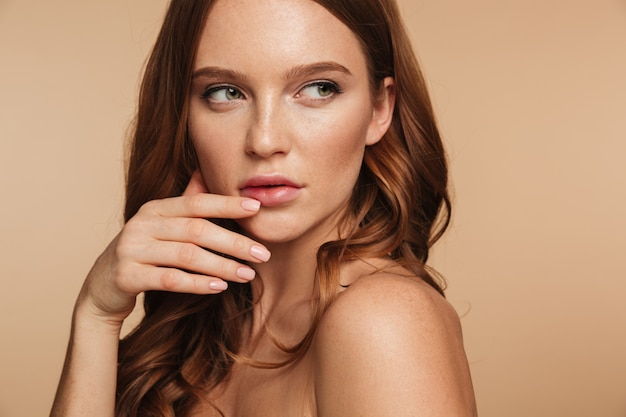 Close up beauty portrait of mystery ginger woman with long hair posing sideways while looking away