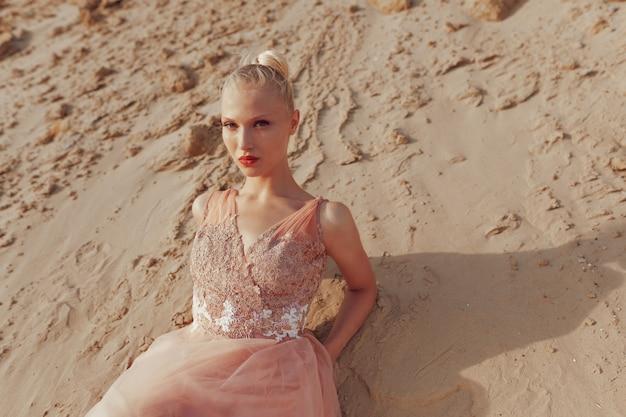 Макро портрет красоты красивой блондинки молодой женщины, позирующей в элегантном платье в пустыне, лежа на золотом песке, глядя в камеру. свет заката.