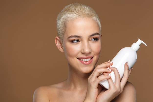 Крупным планом портрет красоты привлекательной улыбающейся молодой блондинки с короткими волосами, позирует изолированной на коричневом, показывая пустой пластиковый контейнер