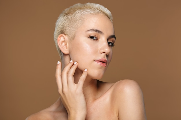 Крупным планом портрет красоты привлекательной улыбающейся молодой блондинки с короткими волосами позирует изолированной на коричневом
