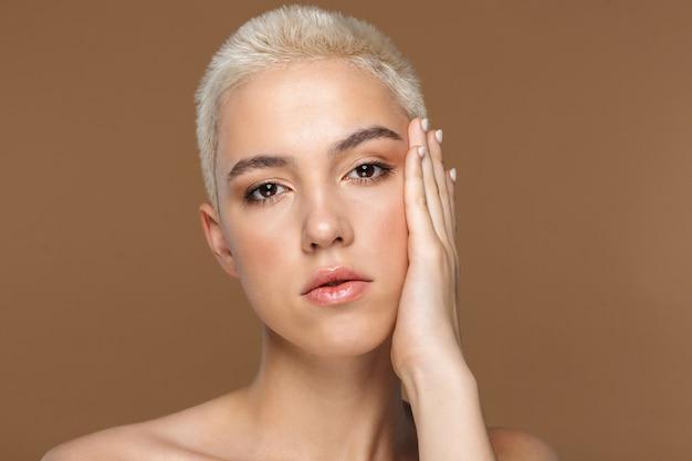 Крупным планом портрет красоты привлекательной молодой блондинки с короткими волосами, позирует изолированными на коричневом фоне