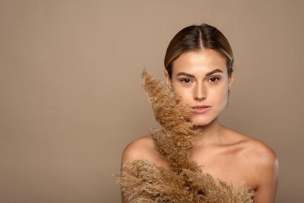 베이지 색 배경 위에 갈색 머리를 가진 매력적인 젊은 토플리스 여자의 아름다움 초상화를 닫습니다