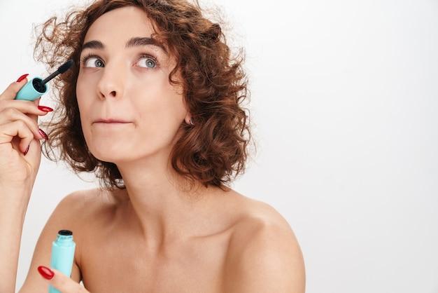 Крупным планом портрет красоты привлекательной молодой женщины топлес с короткими вьющимися каштановыми волосами, изолированными над белой стеной, показывая тушь
