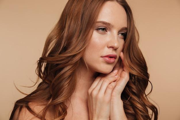 Крупным планом портрет красоты довольно рыжая женщина с длинными волосами, глядя в то время как позирует с руками возле лица
