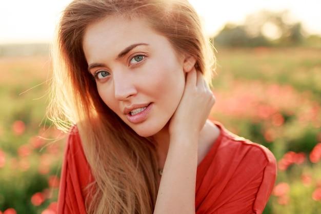 日当たりの良いフィールドでポーズをとって完璧な肌を持つ魅惑的な女性の美しさの肖像画を閉じます。