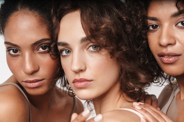흰 벽에 격리된 앞을 바라보는 세 명의 매력적인 젊은 관능적인 다민족 여성의 아름다움 초상화를 클로즈업