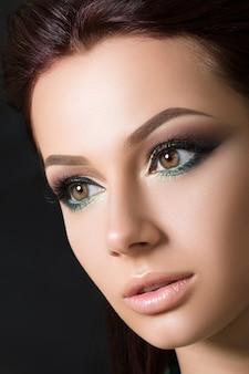 ファッションのスモーキーアイメイクでかなりブルネットの若いモデルのクローズアップの美しさの肖像画。