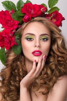 밝은 분홍색 립스틱을 착용하고 그녀의 입술을 만지고 그녀의 머리에 꽃 화 환과 젊은 예쁜 여자의 클로즈업 아름다움 초상화. 밝고 현대적인 여름 메이크업