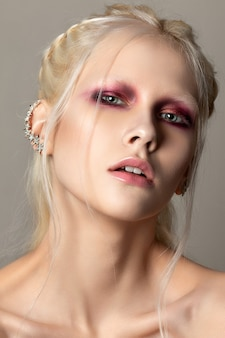 珊瑚の赤いスモーキーな目を持つ若い女性の美しさの肖像画を閉じます。完璧な肌とファッションが構成します。官能性、情熱、トレンディな若者のメイクアップのコンセプト。