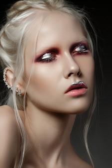 赤と銀のメイクアップで若い女性の美しさの肖像画をクローズアップ。完璧な肌とファッションが構成します。官能性、情熱、トレンディな若者のメイクアップのコンセプト。