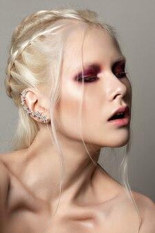 赤いスモーキーな目を持つ若い女性の美しさの肖像画を閉じます。完璧な肌とファッションが構成します。官能性、情熱、トレンディな若者のメイクアップのコンセプト。