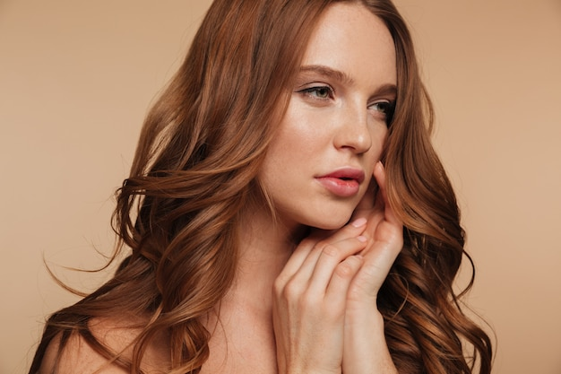 Close up beauty portrait of pretty ginger woman with long hair looking away while posing with arms near face
