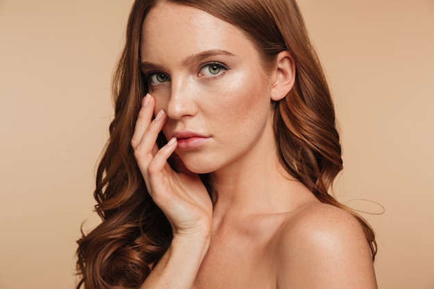 Close up beauty portrait of sensual ginger woman with long hair posing with arm near face while looking