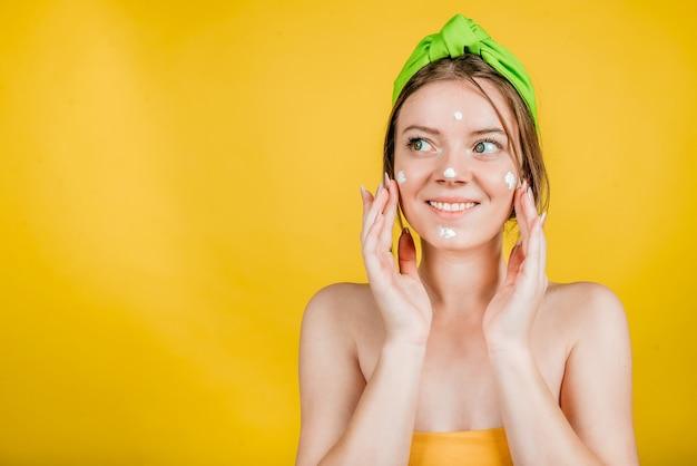 フェイスクリームを適用し、黄色の壁に孤立して目をそらしている美しい半裸の女性の笑顔の美しさの肖像画をクローズアップ。毎日のスキンケアルーチン