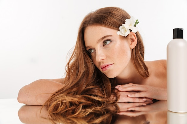 Close up beauty portrait of smiling ginger woman with flower in hair reclines on mirror table with bottle of lotion while looking away