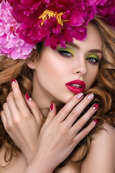 Close-up beauty portrait of young pretty girl with flower wreath in her hair wearing bright pink lipstick and touching her lips. bright modern summer makeup