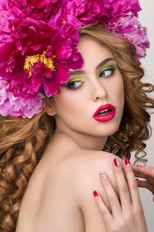 Close-up beauty portrait of young pretty surprised girl with flower wreath wearing bright pink lipstick, touching her lips. bright modern summer makeup.