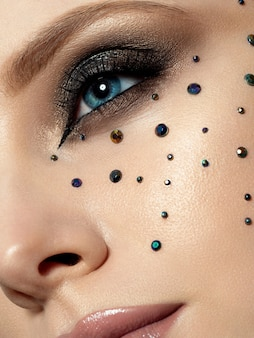 Close up beauty portrait of young woman with beautiful fashion makeup. modern fashion makeup. long lashes, bronze smokey eyes, black rhinestones. extreme closeup, partial face view