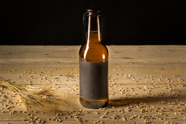 Close-up of a beer bottle and ears of wheat on woodgrain