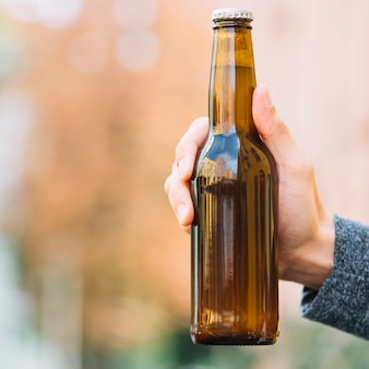 Close-up of a beer bottle in hand